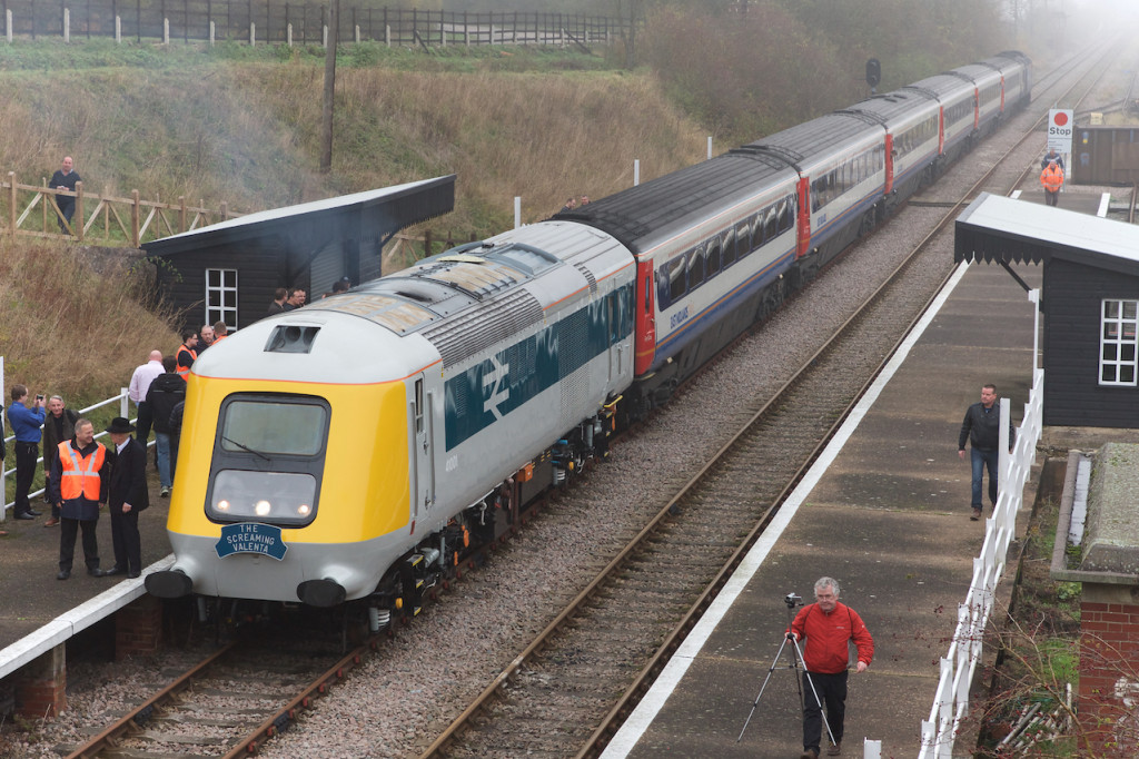 Prototype Power Car 41001 leading an East Midlands Trains HST, working 'The Screaming Valenta', its Project Miller charity launch train, during a photo stop at Rushcliffe Halt GCR(N), with nosecone and livery designer Sir Kenneth Grange standing hatted and suited alongside, 15th November 2014. Photo Copyright Richard Gennis.